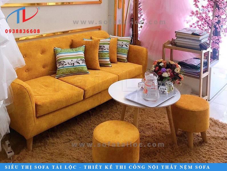 May bọc sofa ở Tân Phú - mẫu ghế băng được bọc lại bằng vải nhung màu vàng sang trọng và nổi bật đặt trong tiệm áo cưới của chị.